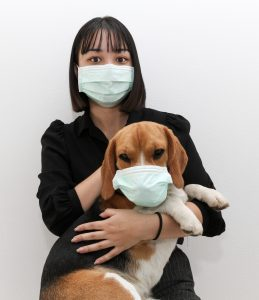 Woman in medical face mask holds a dog wearing medical mask as well